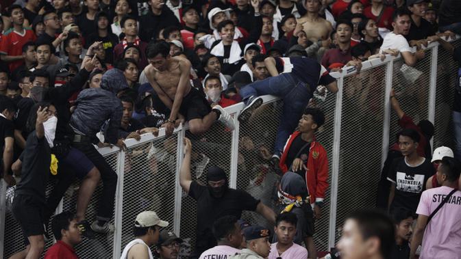 Suporter Timnas Indonesia memanjat pembatas untuk menghampiri suporter Malaysia saat laga Kualifikasi Piala Dunia 2022 di SUGBK, Jakarta, Kamis (5/9). (Bola.com/Vitalis Yogi Trisna)