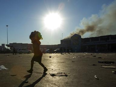 Seorang wanita membawa bahan makanan di kepalanya hasil menjarah dari toko terdekat di kompleks perbelanjaan Naledi di Vosloorus, timur Johannesburg, Senin (12/7/2021). Kerusuhan dan penjarahan yang dipicu penahanan mantan Presiden Afrika Selatan Jacob Zuma. (AP/Themba Hadebe)