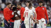Para pemain Timnas Inggris berusaha menenangkan Bukayo Saka yang gagal mengekusi penalti saat melawan Italia pada laga final Euro 2020 di Stadion Wembley, London, Senin (12/07/2021). (Foto: AP/Carl Recine,Pool)