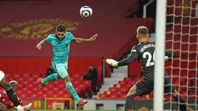 Gelandang Liverpool, Roberto Firmino (tengah) melepaskan sundulan yang berbuah gol kedua timnya ke gawang Manchester United dalam laga lanjutan Liga Inggris 2020/2021 pekan ke-35 di Old Trafford, Kamis (13/5/2021). Liverpool menang 4-2 atas Manchester United. (AFP/Dave Thompson/Pool)