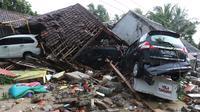 Tiga unit mobil tertimbun reruntuhan rumah yang rusak setelah tsunami menerjang kawasan Anyer, Banten, Minggu (23/12). Tsunami menerjang pantai di Selat Sunda, khususnya di daerah Pandenglang, Lampung Selatan, dan Serang. (Liputan6.com/Angga Yuniar)