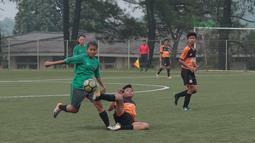 Aksi pemain Villa 2000 menghalau bola dari kaki pemain Timnas Wanita Indonesia pada laga uji coba di Lapangan Sawangan, Depok, Kamis (19/4/2018). Timnas Wanita Indonesia kalah 1-2. (Bola.com/Nick Hanoatubun)