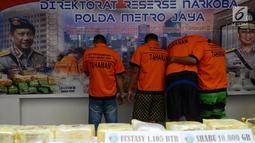 Sejumlah tersangka kasus narkoba menutupi wajah mereka saat gelar perkara di Polda Metro Jaya, Jakarta, Jumat (1/3). Subdit II Resnarkoba menyita sabu seberat 10 Kg dan 1.105 butir ekstasi jenis diamond. (Merdeka.com/ImamBuhori)