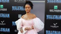 "Rihanna berpose untuk fotografer pada pemutaran perdana ""Valerian and The City of a Thousand Planets"" di Los Angeles, 17 Juli 2017. Penampilan Rihanna dengan gaun ekor yang menjuntai panjang menciptakan efek dramatis. (Neilson Barnard/GETTY IMAGES/AFP)"