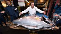 Pengusaha restoran sushi Jepang, Kiyoshi Kimura memamerkan ikan tuna sirip biru seberat 276 kilogram di restoran utamanya di Tokyo, Minggu (5/1/2020). Tuna raksasa itu dibeli dalam lelang perdana 2020 dengan harga USD 1,8 juta atau sekitar Rp 24 miliar. (Kazuhiro NOGI / AFP)