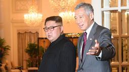 Perdana Menteri Singapura, Lee Hsien Loong menyambut kedatangan pemimpin Korea Utara Kim, Jong-un di Istana Kepresidenan Singapura, Minggu (10/6). Kim Jong Un dan Donald Trump akan bertemu pada 12 Juni. (AFP Photo/Roslan Rahman)