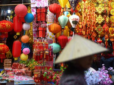 Wanita Vietnam melihat-lihat dekorasi Tahun Baru Imlek atau perayaan Tet di sebuah pasar pusat Kota Tua Hanoi, Senin (28/1). Di Vietnam, tahun baru imlek dikenal dengan nama Tet Nguyen Dan atau lebih akrab disingkat sebagai Tet. (Manan VATSYAYANA/AFP)