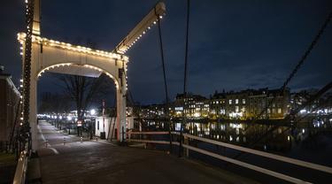Sebuah jembatan yang sepi terlihat selama jam malam di pusat kota Amsterdam, Sabtu (23/1/2021). Belanda memasuki fase terberat dari pembatasan anti-virus Corona hingga saat ini. (AP Photo/ Peter Dejong)