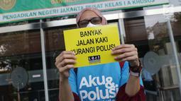Aktivis membentangkan tulisan saat menunggu proses pengajuan gugatan warga untuk menuntut hak mendapatkan udara bersih di Pengadilan Negeri Jakarta Pusat, Kamis (4/7/2019). Mereka mengajukan gugatan warga negara kepada tujuh pihak tergugat. (Liputan6.com/Helmi Fithriansyah)