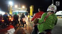 Pemudik bermotor bersiap masuk ke dalam kapal penyeberangan di Dermaga 6 Pelabuhan Merak, Banten, Kamis (22/6). Dini hari, ribuan pemudik bermotor antri menyeberang dari Pelabuhan Merak menuju Bakauheni, Lampung. (Liputan6.com/Helmi Fithriansyah)