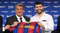 Penyerang Sergio Aguero (kanan) berpose dengan presiden Joan Laporta selama presentasi resminya sebagai pemain baru Barcelona di stadion Camp Nou, Spanyol (31/65/2021).  Barcelona dan Sergio Aguero sama-sama sepakat untuk menyelipkan klausul pelepasan dalam kontraknya. (AFP Photo/Lluis Gene)