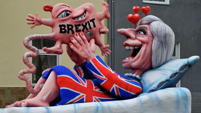 Kereta karnaval membawa karikatur yang menggambarkan Perdana Menteri Inggris, Theresa May melahirkan bayi Brexit-nya dalam parade karnaval Rose Monday di Duesseldorf, Jerman, Senin (12/2). (AP Photo/Martin Meissner)