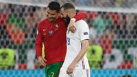 Cristiano Ronaldo dan Karim Benzema berjalan berangkulan ketika selesai babak pertama pertandingan Grup F Euro 2020 antara Portugal melawan Prancis yang berlangsung di Puskas Arena, Budapest, Hungaria pada Rabu (23/06/2021). (AFP/Pool/Franck Fife)