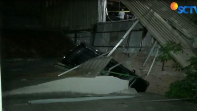 Sebuah rumah rusak setelah tertimpa mobil dari lantai 3, areal parkir Pasar Jaya Mulya, Simpang Tiga, Penggilingan.