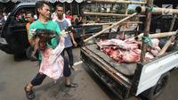 Petugas membawa daging kambing yang sudah dipotong untuk dibagikan di Masjid Sunda Kelapa, Jakarta, Jumat (1/9). Daging tersebut akan dibawgikan kepada yayasan dan warga. (Liputan6.com/Immanuel Antonius)