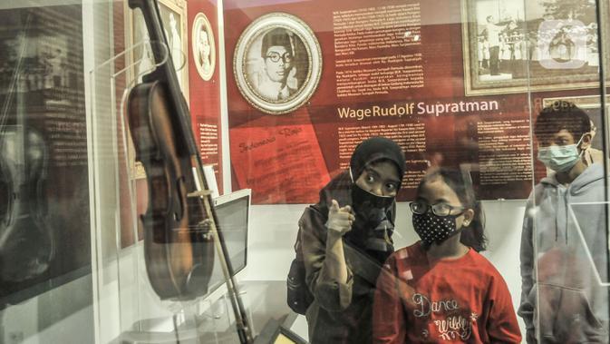 Orang tua membimbing anaknya melihat salah satu koleksi sejarah di Museum Sumpah Pemuda, Jakarta, Rabu (28/10/2020). Libur cuti bersama dimanfaatkan untuk mengajak anak-anak mengenal sejarah lahirnya Sumpah Pemuda agar memahami jejak perjuangan pahlawan sejak dini. (merdeka.com/Iqbal Nugroho)