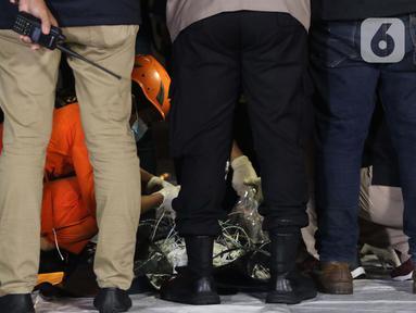 Petugas Basarnas bersama tim DVI Polri mengecek barang temuan yang diduga serpihan pesawat Sriwijaya Air SJ 182 di Dermaga JICT 2, Jakarta, Minggu (10/1/2021) dini hari. Sriwijaya Air SJ 182 hilang kontak empat menit usai lepas landas dari Bandara Soetta. (Liputan6.com/Helmi Fithriansyah)
