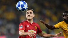 Bek Manchester United, Diogo Dalot berebut bola dengan striker Young Boys, Roger Assale selama pertandingan grup H Liga Champions di The Stade de Suisse di Bern (19/9). Dalot menjalani debutnya dengan MU di pertandingan ini.  (AFP Photo/Fabrice Coffrini)