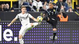 Pemain Jerman, Marcel Halstenberg, berebut bola dengan pemain Argentina, Roberto Pereyra, pada laga persahabatan di Stadion Signal Iduna Park, Rabu (9/10). Kedua tim bermain imbang 2-2. (AP/Martin Meissner)