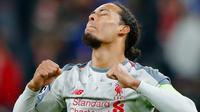 Bek Liverpool, Virgil Van Dijk berselebrasi setelah menang atas Bayern Munchen pada leg kedua babak 16 besar Liga Champions di Allianz Arena, Rabu (13/3). Liverpool lolos ke perempat final setelah menang 3-1 atas Bayern Munchen. (AP/Matthias Schrader)