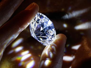 Model memegang sebuah berlian tanpa cela seukuran stroberi besar di rumah lelang Sotheby's, London, 8 Februari 2018. Berlian 102 karat dengan bentuk sempurna itu akan dijual dalam sebuah lelang di Kota London pada Februari ini. (AP/Alastair Grant)