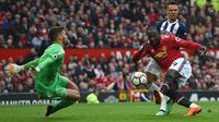 Striker Manchester United (MU) Romelu Lukaku (kanan) melepas tembakan yang dihentikan kiper West Bromwich Albion Ben Foster pada laga di Old Trafford, Minggu (15/4/2018). (AFP/Paul Ellis)