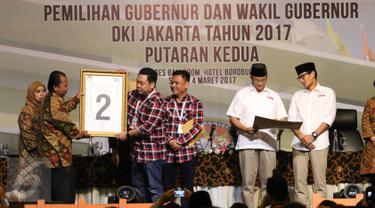 Perwakilan dari cagub dan cawagub no. 2 Pasangan Basuki Tjahaja Purnama atau Ahok dan Djarot Saiful Hidayat menerima plakat yang diberikan oleh ketua KPU DKI Jakarta, Sumarno saat rapat pleno terbuka di Jakarta, Sabtu (5/3). (Liputan6.com/Angga Yuniar)