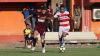Duel antara bek PSM Makassar, Aaron Evans (kiri), dengan striker Madura United, Alberto Goncalves, dalam leg kedua semifinal Piala Indonesia 2018 di Stadion Gelora Madura, Pamekasan, Minggu (7/7/2019). (Bola.com/Aditya Wany)