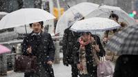 Warga menggunakan payung berjalan selama hujan salju lebat di Tokyo (22/1). Hujan salju membuat keberangkatan penerbangan dan melumpuhkan beberapa layanan kereta api di kota tersebut. (AFP Photo/Behrouz Mehri)