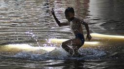Seorang anak bermain di genangan air terowongan Apron Kemayoran, Jakarta, Selasa (11/9). Terowongan Apron, Jalan HBR Motik, Kemayoran, Jakarta Pusat, tergenang air karena ada sumbatan di saluran air dari 2 minggu lalu. (Liputan6.com/Herman Zakharia)