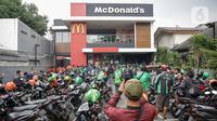 Kerumunan pengemudi ojek online saat antre mengambil pesanan di gerai cepat saji McDonald's Raden Saleh, Jakarta, Rabu (9/6/2021). Puluhan driver ojek online terlihat mengabaikan protokol kesehatan saat mengantre pesanan BTS Meal yang mulai dijual. (Liputan6.com/Faizal Fanani)