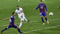 Penyerang Real Madrid, Karim Benzema melakukan tendangan dibayangi pemain Eibar pada laga lanjutan Liga Spanyol di Stadion Ipurua, Senin dinihari WIB (21/12/2020). Benzema menjadi pahlawan dalam kemenangan Madrid karena menciptakan satu gol dan dua assist di laga tersebut. (AP/Alvaro Barrientos)