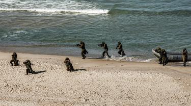 Pejuang bersenjata turun dari perahu karet di pantai selama latihan militer di Kota Gaza (29/12/2020).  Untuk pertama kalinya, Hamas bersama sayap militer kelompok-kelompok perlawanan Palestina lainnya menggelar latihan perang gabungan. (AFP/Mohammed Abed)
