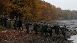 Para nelayan menarik tali yang mengarah pada jaring berisi ikan mas ketika panen ikan secara tradisional di kolam Horusicky, dekat kota Veseli nad Luznici, Republik Ceko, 24 Oktober 2017. (AP Photo/Petr David Josek)