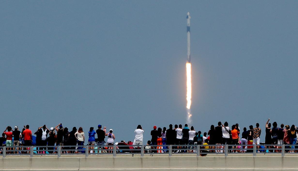 Penonton menyaksikan dari jembatan di Titusville ketika SpaceX Falcon 9 lepas landas dari Pusat Antariksa Kennedy di Cape Canaveral, Florida, Sabtu (30/5/2020). Roket itu membawa pesawat luar angkasa Crew Dragon beserta awaknya dua astronot Douglas Hurley dan Robert Behnken.  (AP/Charlie Riedel)