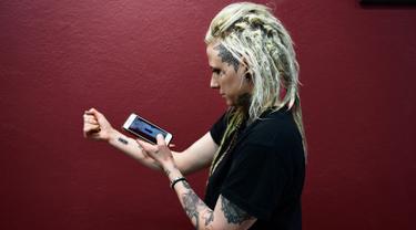 Hanna Washlake mendengarkan tato gelombang suara yang mengeluarkan pesan dari ibunya di Black Raven Tattoo California, 12 April 2018. Soundwave Tattoo menghasilkan suara berdurasi satu menit yang berasal dari pola gelombang audio. (AFP/FREDERIC J. BROWN)