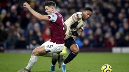 Pemain Manchester United Anthony Martial (kanan) berebut bola dengan pemain Burnley James Tarkowski pada pertandingan Liga Inggris di Turf Moor, Burnley, Inggris, Sabtu (28/12/2019). MU menang 2-0 dan melonjak ke posisi lima klasemen. (Martin Rickett/PA via AP)