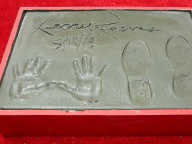 Cetakan tangan dan kaki aktor Keanu Reeves dalam upacara pembuatan cetakan tangan dan kaki di TCL Chinese Theatre, Los Angeles, Selasa (14/5/2019). Aktor 54 tahun itu mendapat penghargaan membuat cetakan tangan dan kaki untuk merayakan keberhasilan karirnya dalam film. (Willy Sanjuan/Invision/AP)