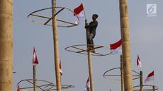 Pekerja memasang bendera Merah Putih pada pohon pinang untuk acara panjat pinang kolosal di kawasan Ancol, Jakarta, Kamis (15/8/2019). Ancol Taman Impian menggelar berbagai acara dalam menyambut HUT ke-74 RI, salah satunya adalah Panjat Pinang Kolosal. (Liputan6.com/Herman Zakharia)