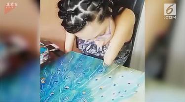 Seorang wanita yang juga penyandang disabilitas melukis burung merak tanpa bantuan orang lain.