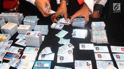 Petugas merapihkan E-KTP di Mapolres Bogor, Cibinong (28/4). Saat ini E-KTP yang tercecer sebanyak satu dus dan seperempat karung  dijadikan barang bukti kepolisian Resort Bogor. (Merdeka.com/Arie Basuki)