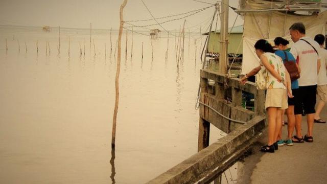 Penduduk setempat membeli dagangan Nguyen Thi Ro