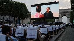 Sebuah film gratis yang diputar di ruang terbuka di jalan Champs Elysees, Paris (7/7/2019). Bioskop terbuka ini menyediakan 1800 kursi bagi penonton yang ingin menyaksikan film-film gratis yang ditayangkan. (AP Photo/Michel Euler)