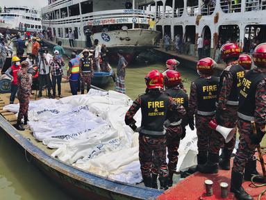Petugas pemadam kebakaran mengumpulkan jenazah korban kecelakaan kapal feri di Sungai Buriganga, Dhaka, Bangladesh, Senin (29/6/2020). Sebanyak 32 orang tewas dan banyak lainnya masih dinyatakan hilang dalam insiden kapal feri tenggelam di Bangladesh. (AP Photo/Al-emrun Garjon)