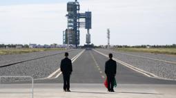 Para pejabat berdiri di landasan jelang peluncuran roket Long March-2F Y12 yang membawa pesawat ruang angkasa Shenzhou-12 di Pusat Peluncuran Satelit Jiuquan, China, Kamis (17/6/2021). Di stasiun ruang angkasa nanti, mereka akan melakukan tugas selama tiga bulan ke depan. (AP Photo/Ng Han Guan)