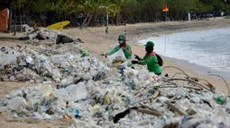 Pekerja mengumpulkan sampah plastik saat membersihkan pantai Kuta dekat Denpasar di pulau wisata Bali (6/1/2021). Pada 1 Januari 2021, sekira 30 ton sampah diangkut dari kawasan Pantai Kuta dalam kegiatan bersih-bersih pantai. (AFP/Sonny Tumbelaka)