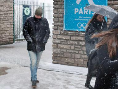 Pejalan kaki berjalan saat turun salju di Paris, Prancis, (6/2). Badan cuaca nasional Prancis Meteo France mengatakan sekitar setengah negara di eropa siaga atas bahaya tingkat salju dan es yang berbahaya. (AP Photo / Francois Mori)
