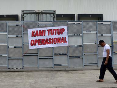 Warga melewati di spanduk 'Kami Tutup Operasional' di pabrik pengolahan ikan Pelabuhan Muara Baru, Jakarta, Senin (10/10). Mogok massal karena dibatasinya masa sewa di pelabuhan selama 5 tahun yang tadinya selama 20 tahun.  (Liputan6.com/Gempur M Surya)