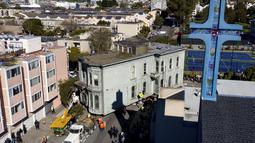 Sebuah truk menarik rumah bergaya Victoria yang dibangun pada tahun 1882 di jalanan San Francisco, Minggu (21/2/2021). Warga berbaris di trotoar untuk mengambil foto saat rumah itu berjalan dengan kecepatan 1,7 km/jam ke 635 Fulton St. (AP Photo/Noah Berger)
