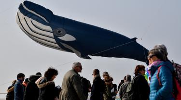 Orang-orang menghadiri Festival Layang-Layang Internasional ke-33 di Berck-sur-Mer, Prancis utara, Sabtu (6/4/2019). Festival Layang-Layang Internasional ini diselenggarakan setiap bulan April dan berlangsung selama 10 hari.  (Photo by Philippe HUGUEN / AFP)